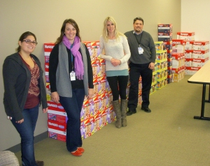Leah Garbe (second from left) and Bill Betts (far right) and volunteers stand next to the wall of diapers